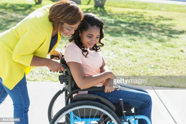 mother with teenage daughter in wheelchair - wheelchair stock pictures, royalty-free photos & images