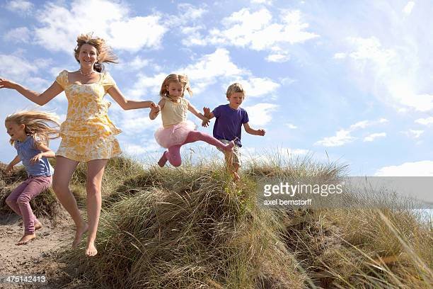 Mother with three children jumping off dunes, Wales, UK