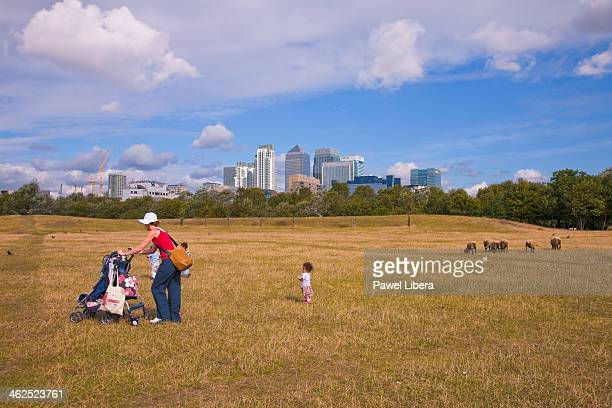 Mother with three children walking through city farm in London Docklands with Canary Wharf Financial Centre in the background
