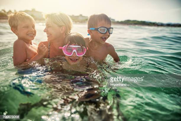 mother with three kids splashing in sea waves - candid beach stock photos and pictures