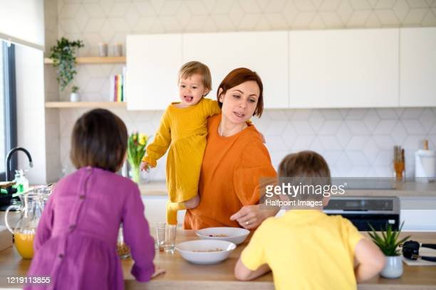 mother with three small children indoors in kitchen in the morning at home. - woman hurry stockfoto's en -beelden