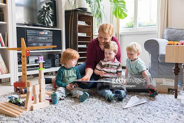 Mother with three toddler boys reading storybook