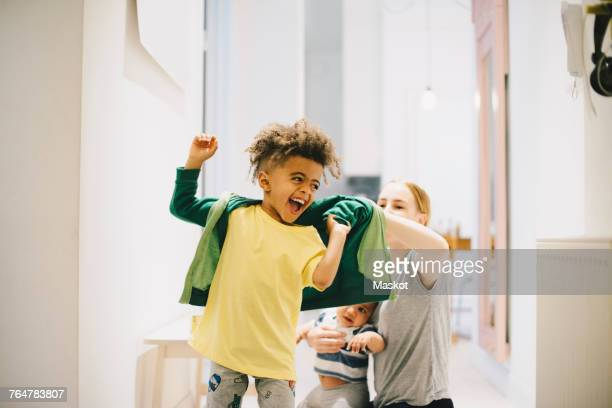 mother with toddler dressing happy son at home - getting dressed stock pictures, royalty-free photos & images