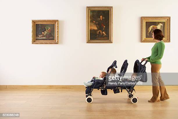 Mother With Triplets Looking at Paintings in Art Gallery