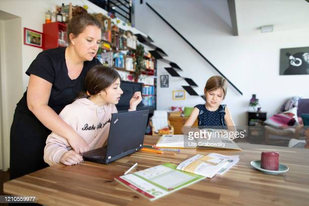 Mother with two children helps doing schoolwork on April 15, 2020 in Bonn, Germany.