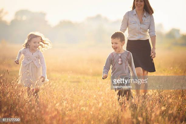 Mother with two children running in the nature