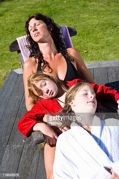 Mother with two children sleeping on lounge chair