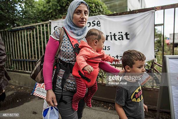 A mother with two children walk inside a temporary tent camp on July 27 2015 in Dresden GermanyThe German Red Cross set up the camp last week and...