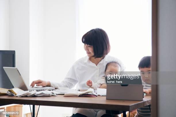 自宅で働く 2 児の母 - 専業主婦 ストックフォトと画像