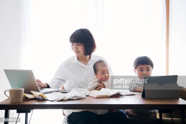 自宅で働く 2 児の母 - シングルマザー ストックフォトと画像