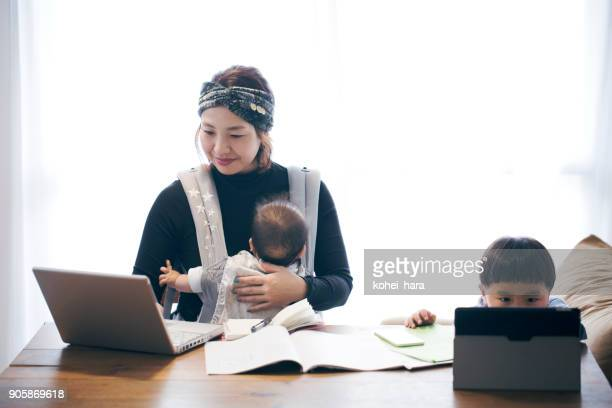 mother with two children working at home - homemaker stock pictures, royalty-free photos & images