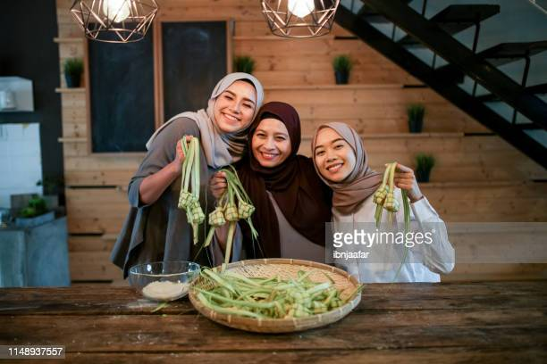 mother with two daughter preparing food in kitchen - eid al adha stock pictures, royalty-free photos & images