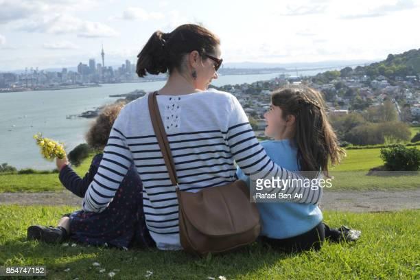 mother with two daughters having fun together outdoors - rafael ben ari stock-fotos und bilder