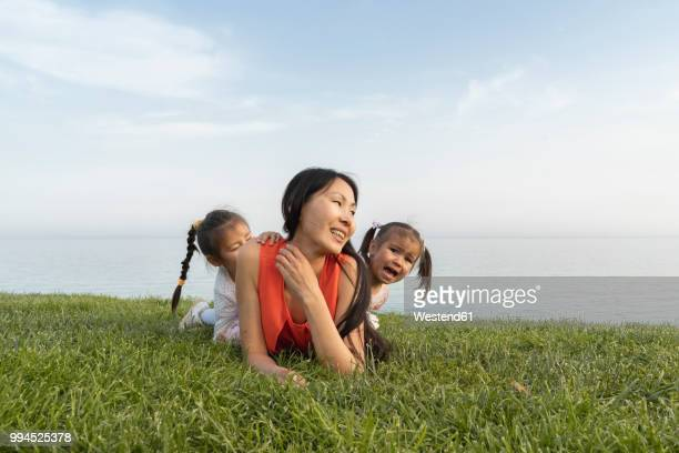 Mother with two daughters lying in grass at the coast