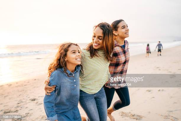 mother with two daughters on the beach - mixed race person stock pictures, royalty-free photos & images