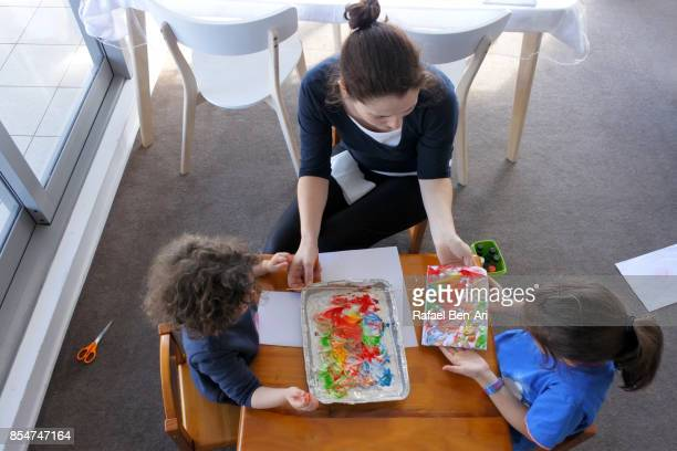 mother with two daughters painting together - rafael ben ari stock-fotos und bilder