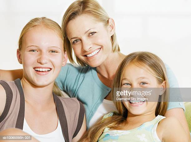 mother with two daughters (9-12 years) sitting on sofa, portrait - 12 13 years stock-fotos und bilder