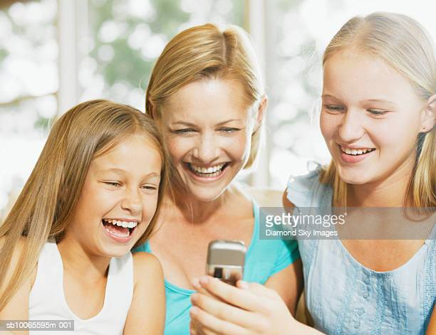 mother with two daughters (9-12 years) using mobile phone indoors - 12 13 years stock pictures, royalty-free photos & images