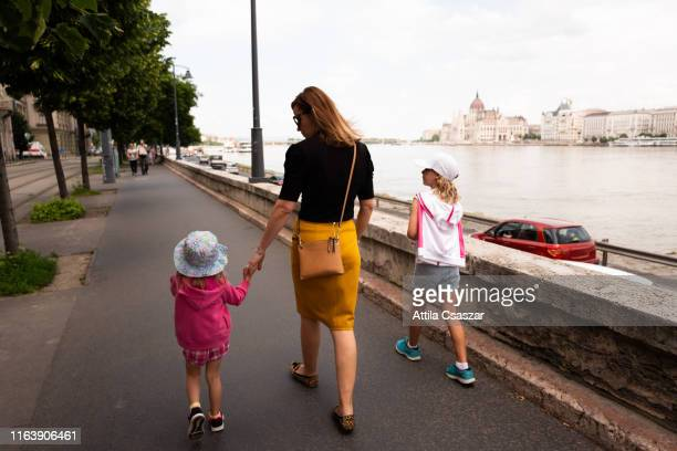 mother with two daughters walking on street - hungary stock pictures, royalty-free photos & images