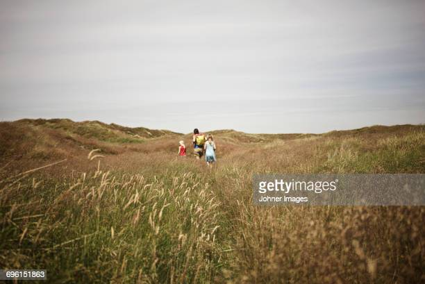 Mother with two daughters walking though meadow