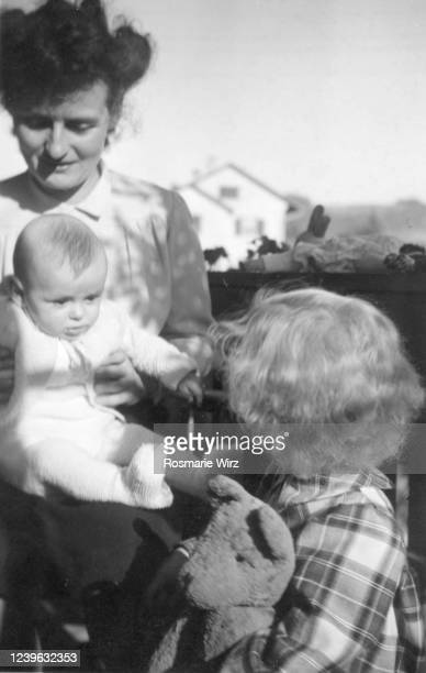 mother with two girls on balcony, 1947 switzerland - 1947 stock pictures, royalty-free photos & images
