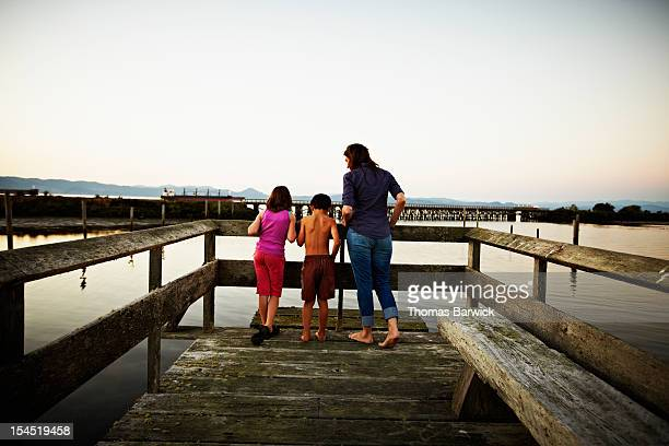 Mother with two kids looking out over dock