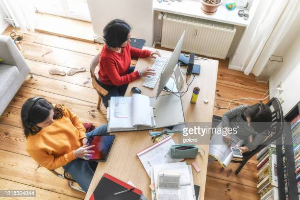 mother with two kids working together at desk in homeoffice - homeschool stock pictures, royalty-free photos & images
