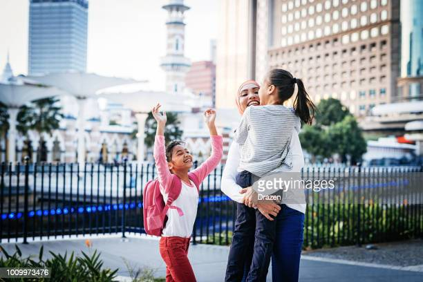 mother with two school kids - malay stock photos and pictures
