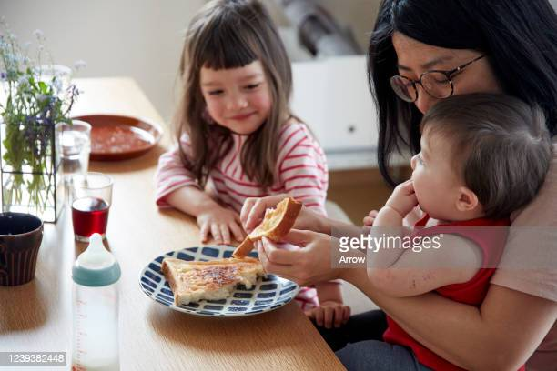 mother with young child and baby eating toast for breakfast - 牛乳ビン ストックフォトと画像