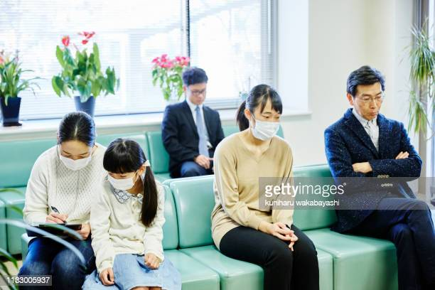 mother with young daughter filling out forms in a hospital waiting room - ミッドアダルト ストックフォトと画像
