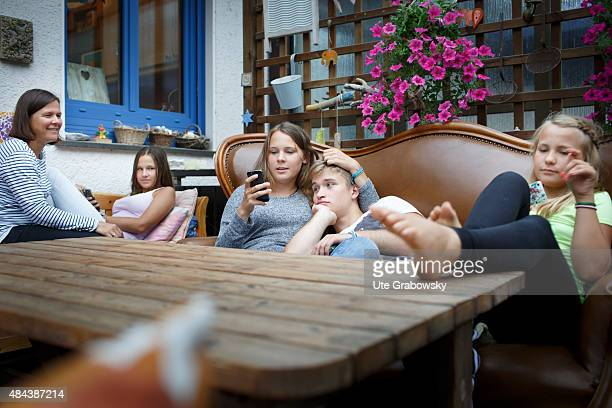 Mother with youth sitting outside on a couch playing with a cellphone on August 10 2015 in Bonn Germany