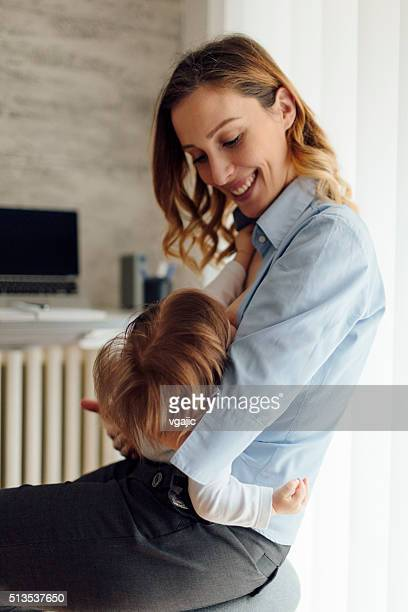 Mother Working and breastfeeding her baby in home office.