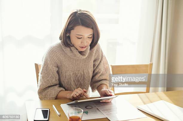 Mother working at home with digital tablet