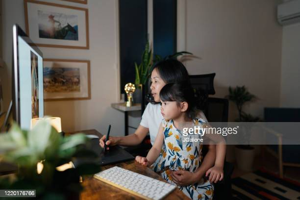 Mother working from her home office at night with her daughter