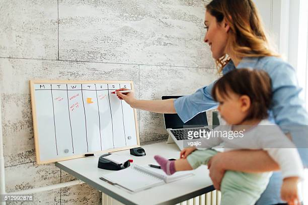 mother working from home and holding her baby - personal organizer stockfoto's en -beelden