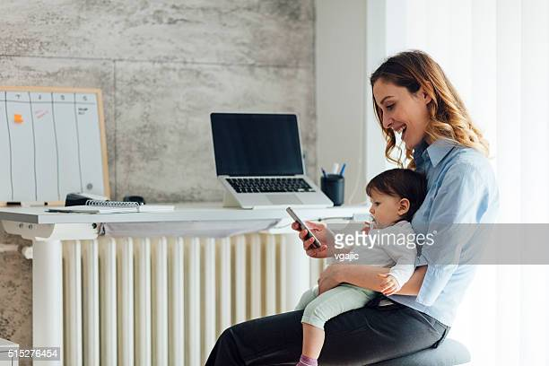 """mother working from home and holding her baby - leanincollection """"working mom"""" stock pictures, royalty-free photos & images"""