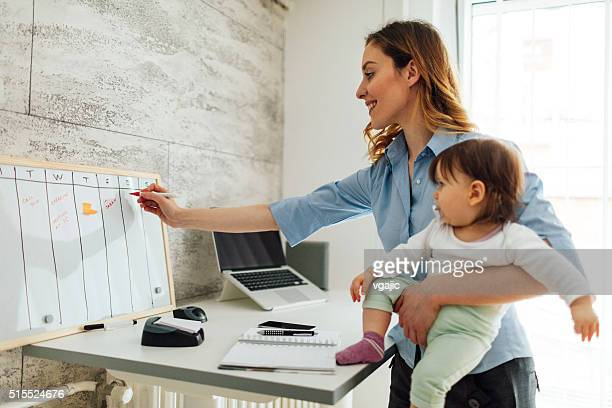 Mother Working From Home And Holding Her Baby