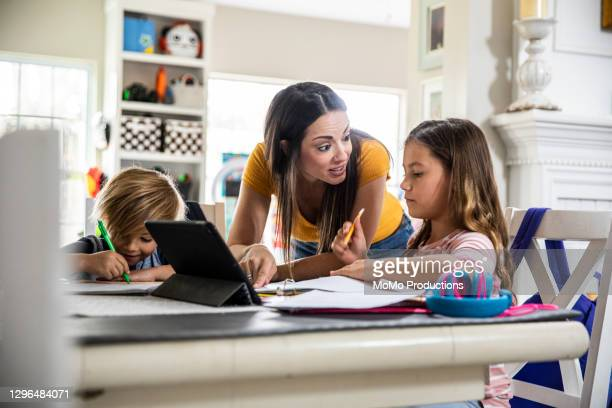 mother working from home and homeschooling children - education stock pictures, royalty-free photos & images