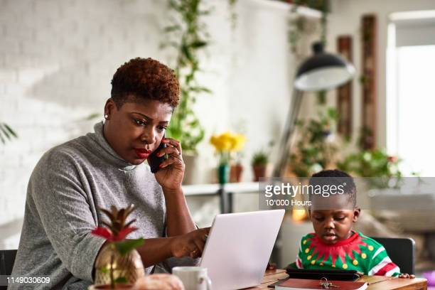 mother working from home on phone with son - serious stock pictures, royalty-free photos & images