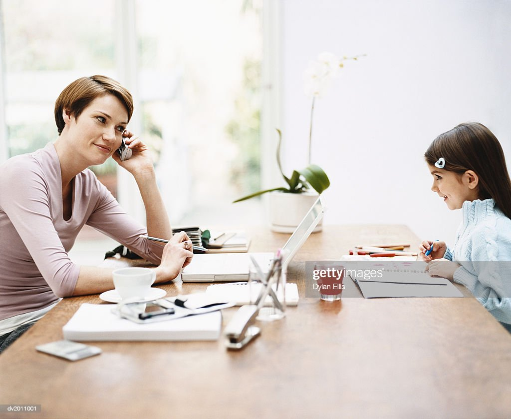 Mother Working From Home Sitting at a Table Opposite Her Daughter Colouring in a Notebook : Stock Photo