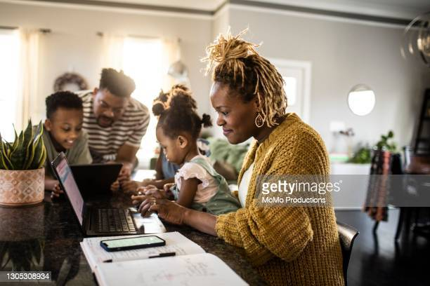 mother working from home while holding toddler, family in background - five people stock pictures, royalty-free photos & images