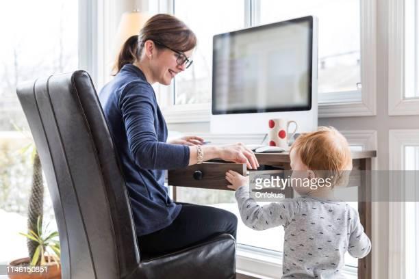 moeder werkt vanuit huis met kid - werk privé balans stockfoto's en -beelden