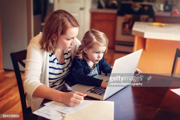 mother working from home with toddler in her lap