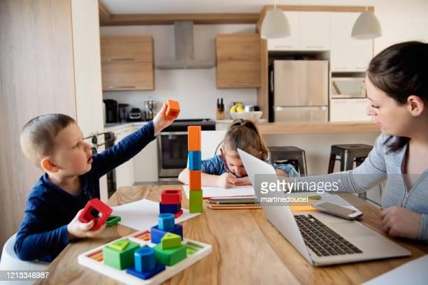 moeder die van huis met jonge kinderen in quarantaineisolatie covid-19 werkt - quarantaine stockfoto's en -beelden