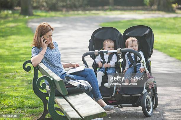 mother working from the park with her young family - pushchair stock pictures, royalty-free photos & images