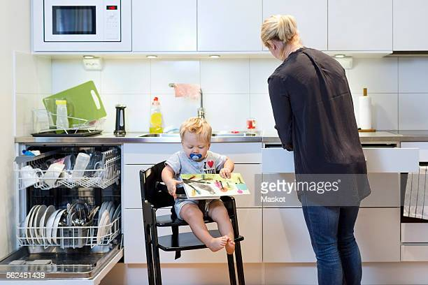 Mother working in kitchen while baby boy sitting on high chair
