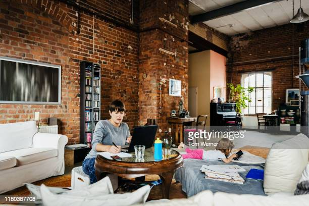 mother working in modern apartment space with daughter playing - premium access stock pictures, royalty-free photos & images