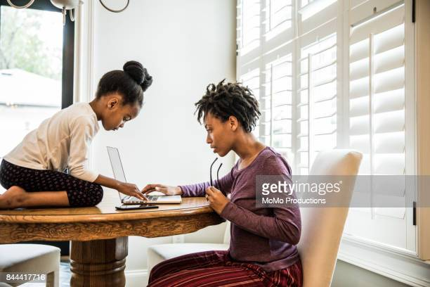 mother working on laptop, daughter on table - stay at home mother stock pictures, royalty-free photos & images