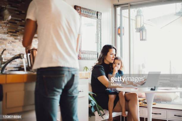 mother working on laptop while daughter looking at father standing in kitchen - working from home stock pictures, royalty-free photos & images