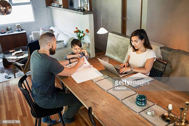 Mother working on laptop while father assisting son in doing homework at dining table